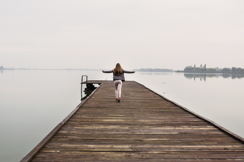Back view of a woman running on a pier at the river and enjoying in a day.