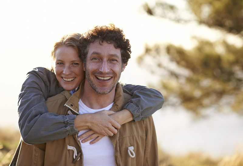 A cropped portrait of a happy affectionate couple standing outdoors on a cold morning